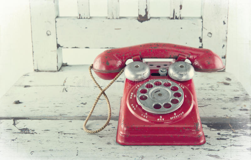 Red toy telephone. On old light blue wooden chair with vintage editing stock photo