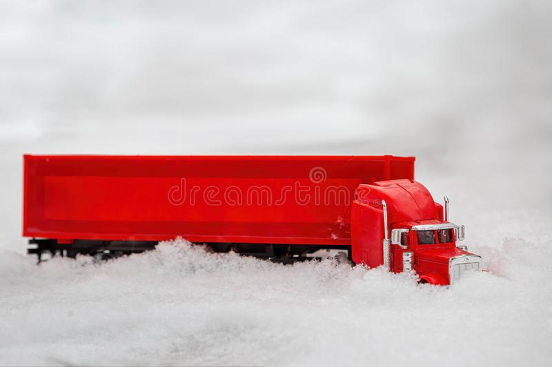 A red toy truck rides in the winter on a snowy road making its way through the snowdrifts. The holiday comes to us. Side view.  royalty free stock photo