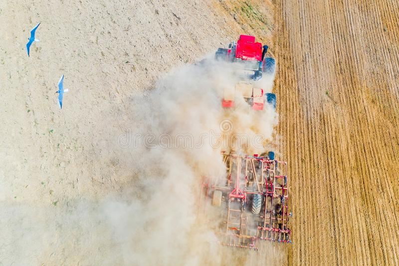 Red tractor cutivating soil on farmland. Aerial landscape. Farming concept royalty free stock photography