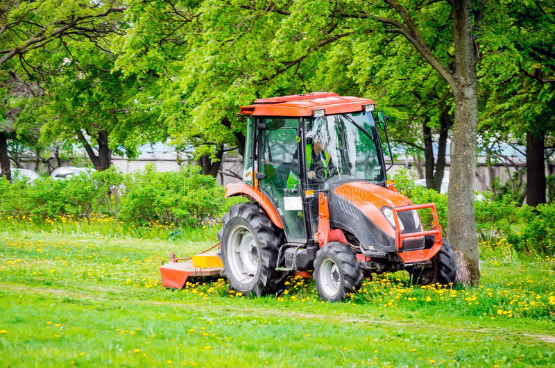 Red tractor and lawn mower, shears lawns in the alleys in the park. royalty free stock image