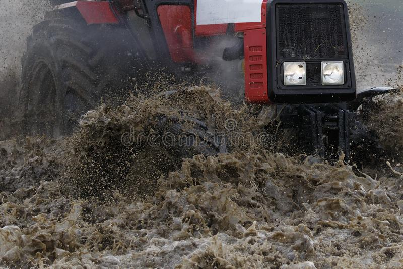 A red tractor moves through a deep puddle, a large amount of water and splashes fly from under the wheels.  royalty free stock photography
