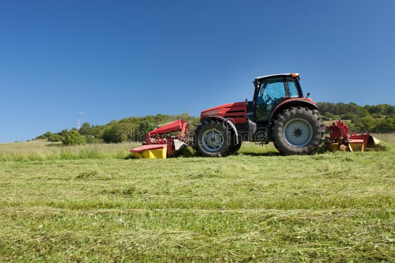 Red tractor mowing the meadow. Summer day, Czech Republic royalty free stock photos