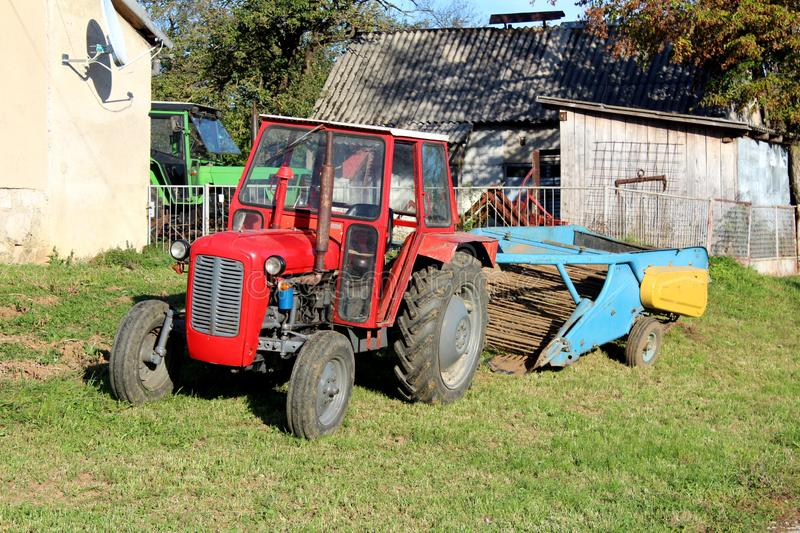 Red tractor parked next to family house with old agricultural equipment in background surrounded with barn and other tractor in. Background on warm sunny day royalty free stock image