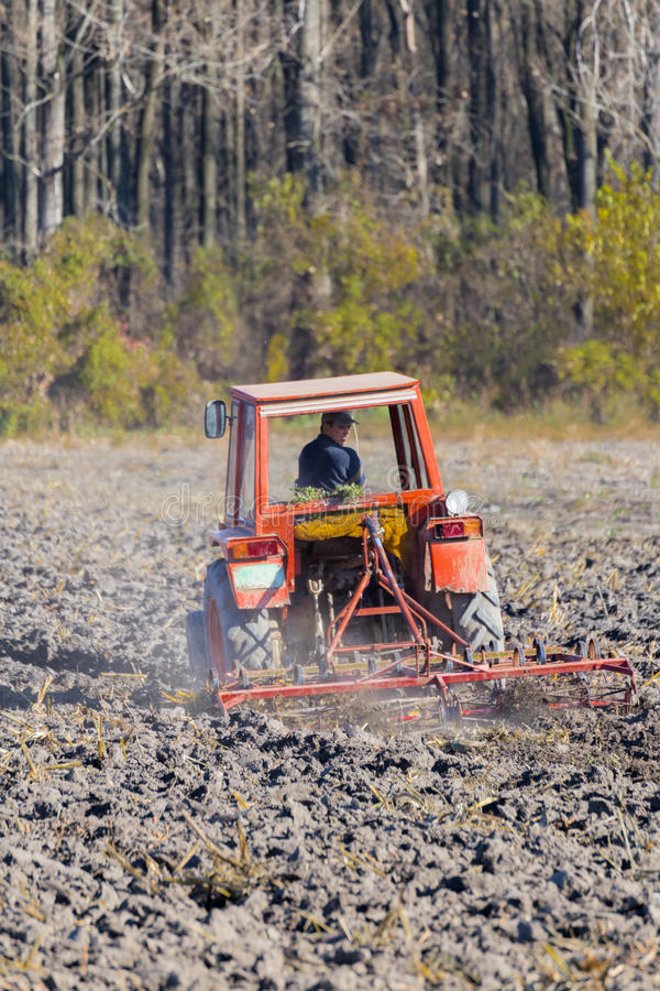 Red Tractor Plowing in Autumn, Preparation Field for Planting stock photography