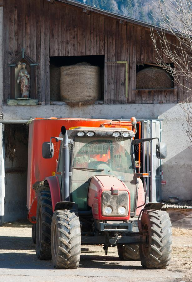Red tractor and religious statue in a farm royalty free stock images