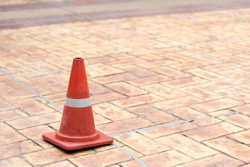 Red traffic cone on tiled rock pavement.  royalty free stock photos
