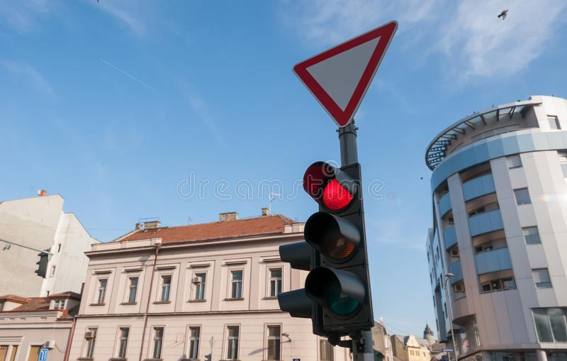 Red traffic light for vehicles and cars on the crosswalk on the street in the city close up with buildings and blue sky background stock photos