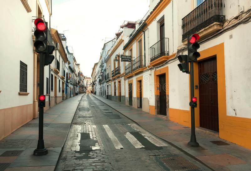 Red traffic lights at morning on empty street of city Cordoba with white wall houses of Andalucia, Spain stock photos