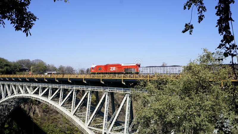 Red train on an iron bridge, Zimbabwe, Africa. stock image
