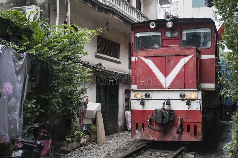 Red train locomotive travels though a narrow street in a poor neighbourhoood of Hanoi. Narrow gap between houses without safety. A red train locomotive travels stock image