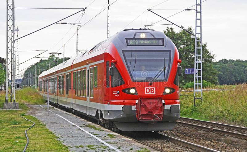 Red Train on Tracks With Green Grass Beside Under Bright Sky stock images