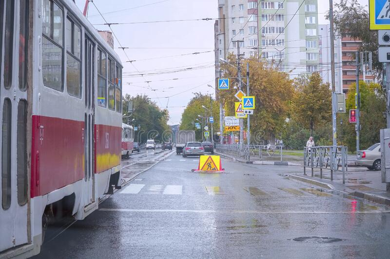 Red tram on a city street on a cloudy, autumnal, rainy day. A road repair sign is visible ahead royalty free stock photography