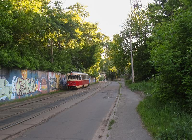 Red tramway in Kiev, Ukraine. Empty street, Forest, Graffiti on the wall royalty free stock image
