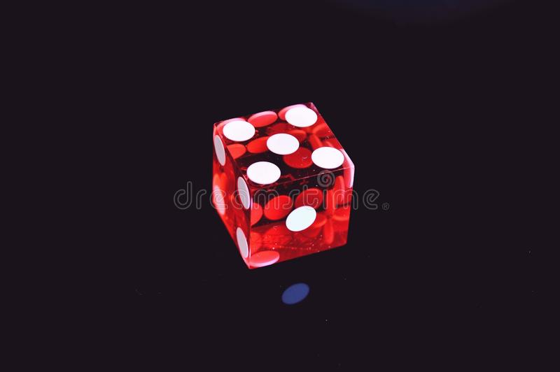 Red Translucent Die on Top of Black Surface royalty free stock image