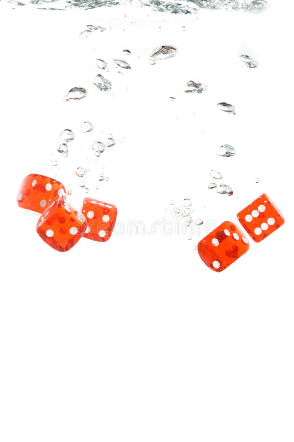 Red transparent dice falling into the water
