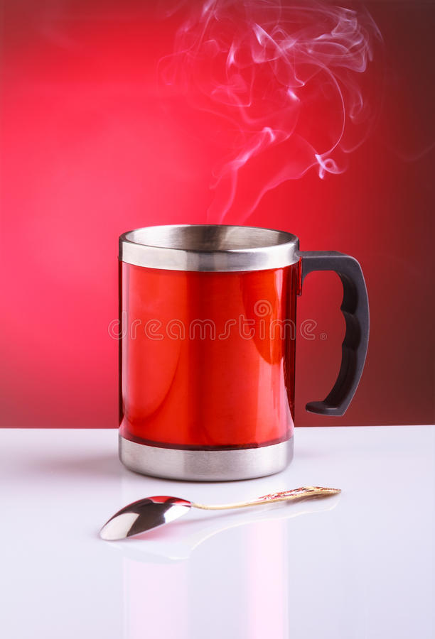 Red travel mug with hot tea and spoon royalty free stock photography
