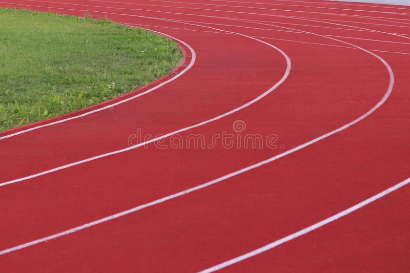 Red treadmill on the football field. Open stadium for sports competitions. Active and healthy lifestyle. Forward movement. Olympic. Competitions. Leisure of the stock photography