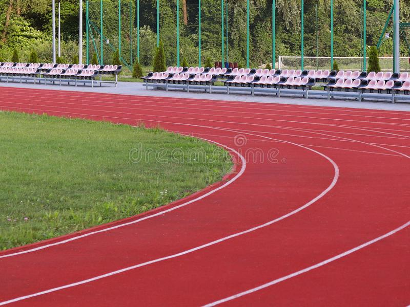 Red treadmill on the football field. Open stadium for sports competitions. Active and healthy lifestyle. Forward movement. Olympic. Competitions. Leisure of the royalty free stock photo