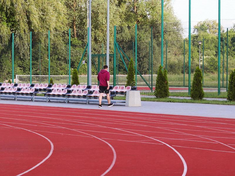 Red treadmill on the football field. Open stadium for sports competitions. Active and healthy lifestyle. Forward movement. Olympic. Competitions. Leisure of the royalty free stock photography