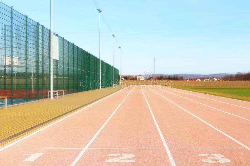 Red treadmill at the stadium. Element of a sports complex. Outdoor coating for sports. A place for competitions in athletics. 1, 2. 3 - start track numbers stock images