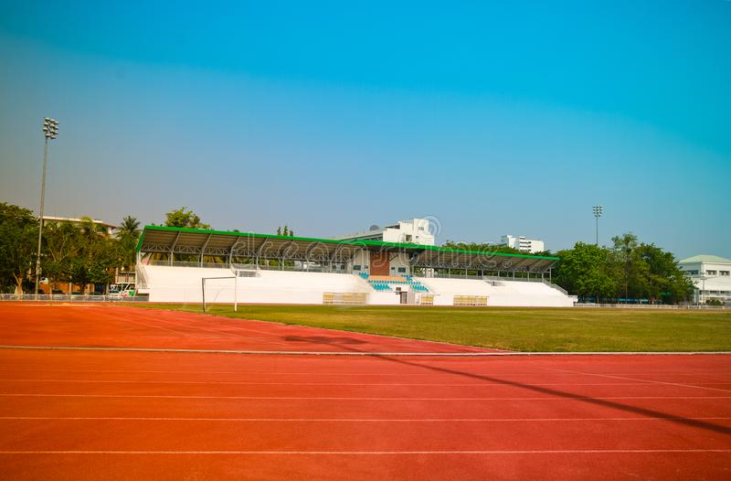 Red treadmill, track running at the stadium with green grass on stock photos