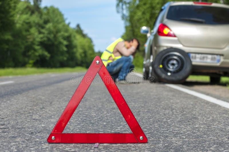 Red triangle sign and Sad man after car breakdown royalty free stock images