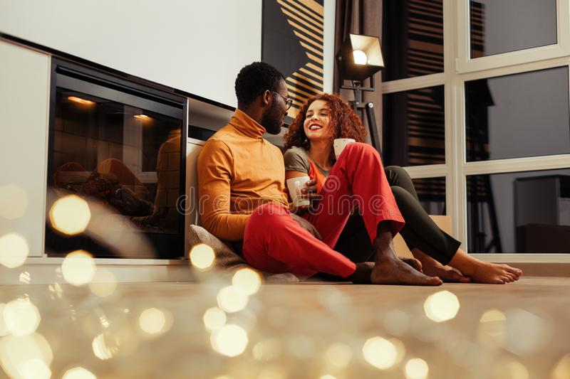 African-American man wearing red trousers sitting near fireplace with wife. Red trousers. African-American men wearing red trousers sitting near fireplace with royalty free stock photo