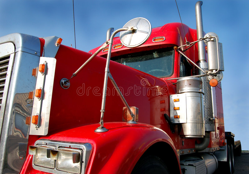 Red Truck. Close-up of front of red semi truck against a blue sky stock images