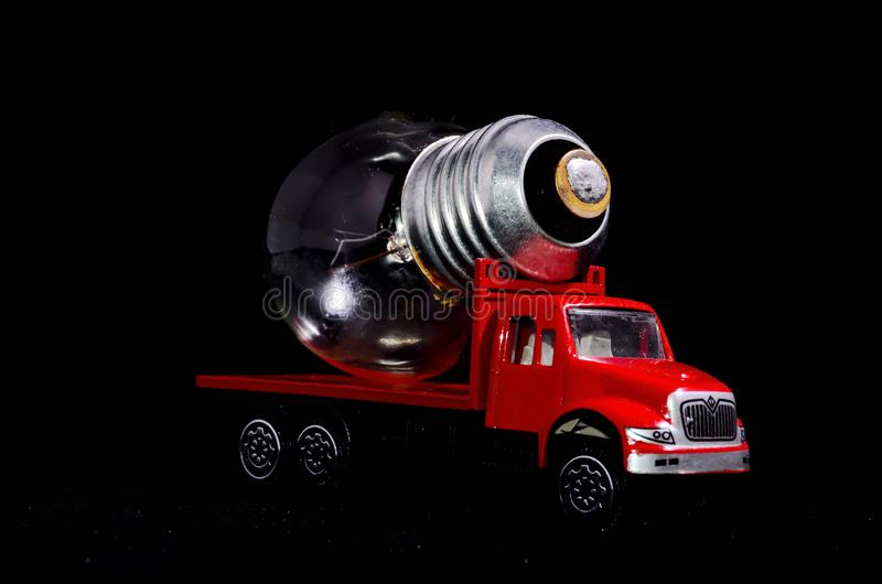 Red Truck Light Bulb. Electric Power Concept Red Truck and Light Bulb on a Black Background stock photos