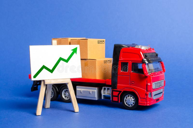 Red truck loaded with boxes and stand with a green up arrow. Raise economic indicators and sales. Exports, imports. High trade. Volumes, growth production stock photos