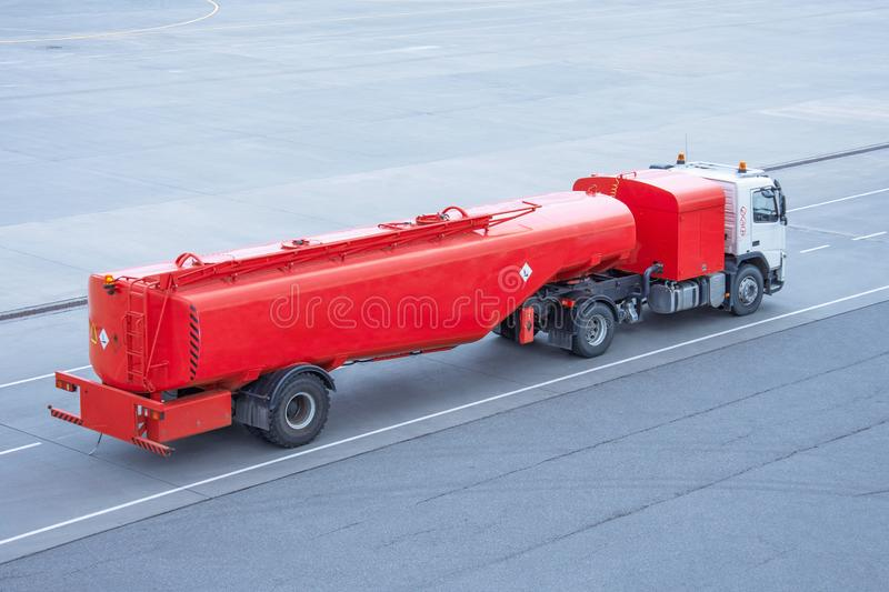 Red truck with a tank and a trailer of aviation fuel on the airport airfield.  royalty free stock photography