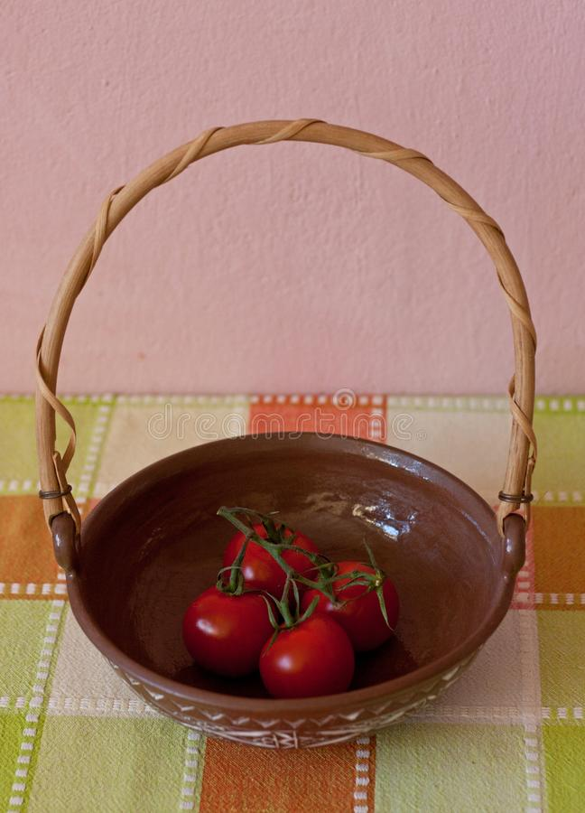 Red truss tomatoes in a bowl on a colorful checked tablecloth against a pink wall stock images