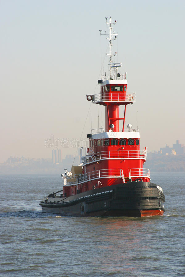 Red Tugboat. Cruising in the harbor stock photography