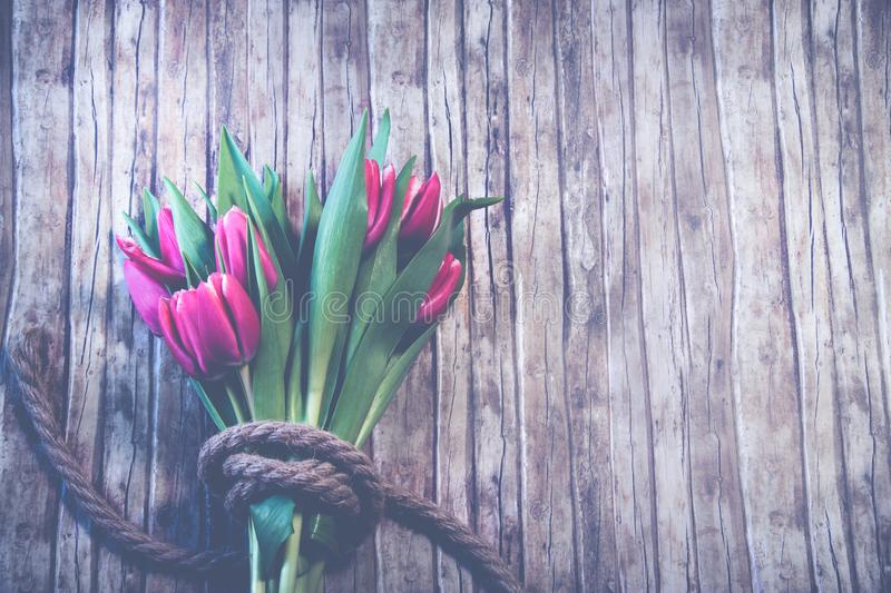 Red Tulip Bouquet on Top of Brown Wooden Surface royalty free stock images