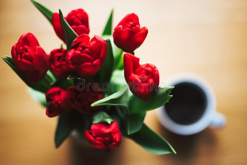 Red Tulip Bouquet Beside White Ceramic Cup Full of Black Liquid stock photo