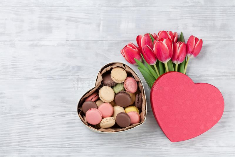 Red tulip flowers and macaroon cookies stock images