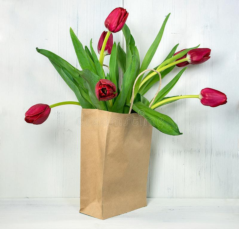 Red tulips in brown sack stock photos