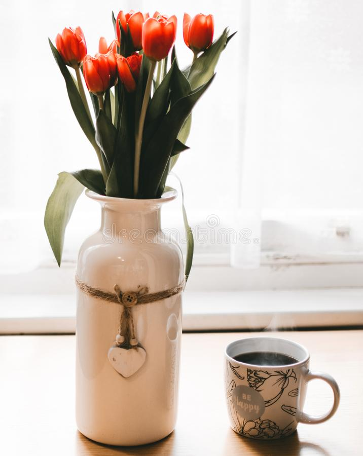 Red Tulips Flowers in White Ceramic Vase Beside Cup of Coffee royalty free stock photo