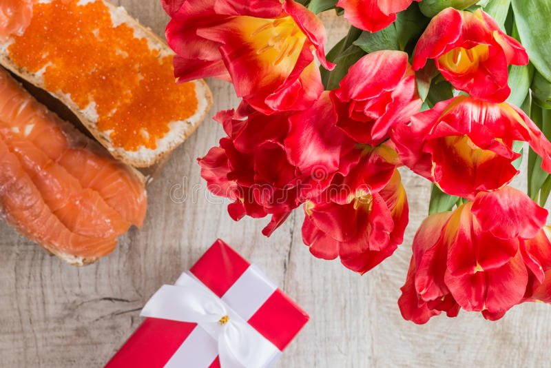 Red tulips, gift and sandwiches with red caviar and salmon on wooden background stock photo
