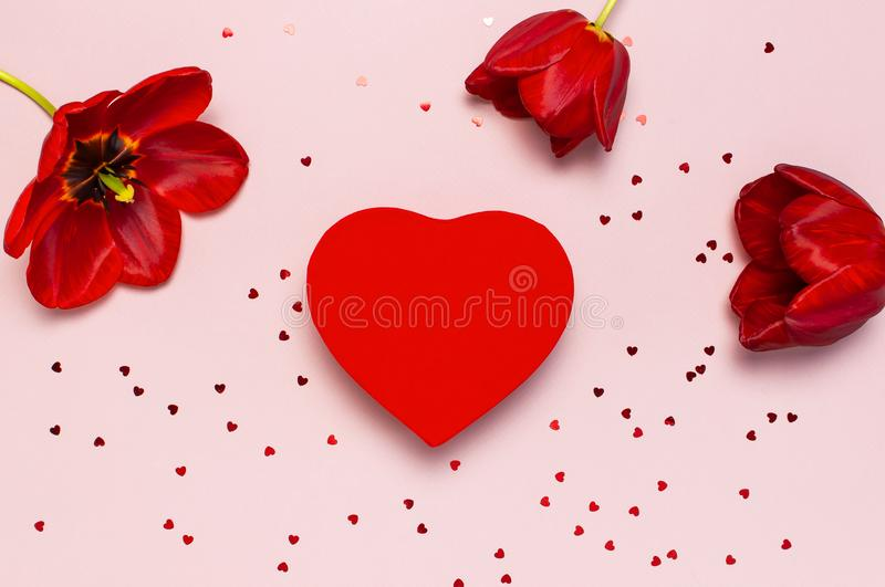 Red tulips, red heart shaped gift box, confetti on pastel pink background top view Flat lay copy space. Mother`s Day, Valentines. Day, birthday, holiday stock photography