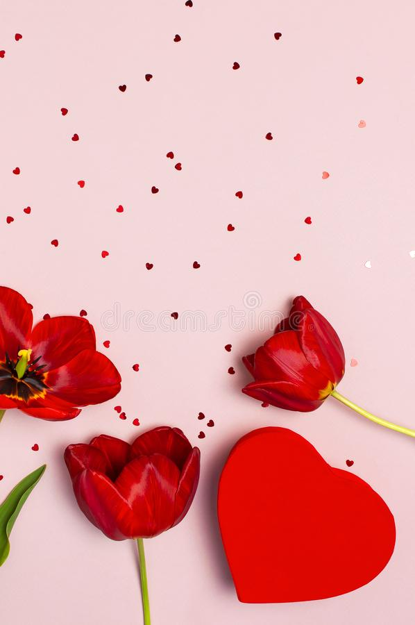 Red tulips, red heart shaped gift box, confetti on pastel pink background top view Flat lay copy space. Mother`s Day, Valentines. Day, birthday, holiday stock images