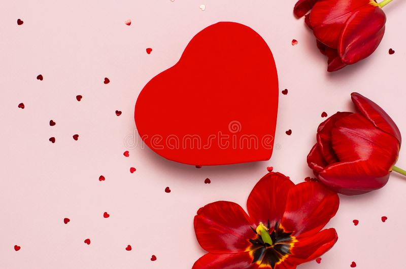 Red tulips, red heart shaped gift box, confetti on pastel pink background top view Flat lay copy space. Mother`s Day, Valentines. Day, birthday, holiday royalty free stock photography