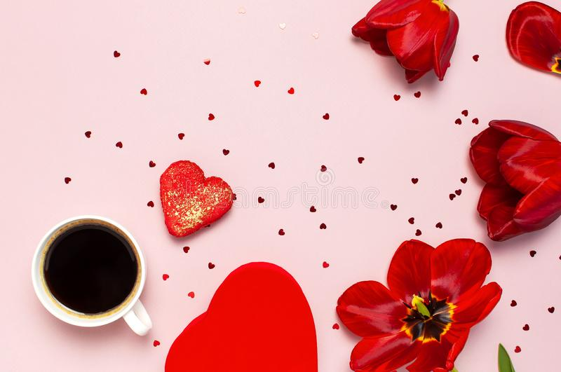 Red tulips, red heart shaped gift box, cup of coffee, macaron cake, confetti on pastel pink background top view Flat lay. Mother` stock images