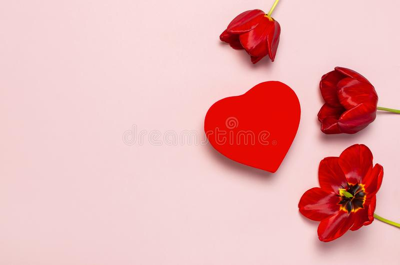 Red tulips, red heart shaped gift box on pastel pink background top view Flat lay copy space. Mother`s Day, Valentines Day,. Birthday, holiday background stock photography