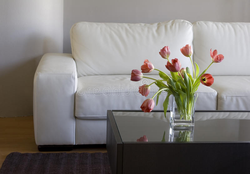 Red tulips in modern living room - home decor. Vase of red tulips in modern white living room - home decor royalty free stock photos