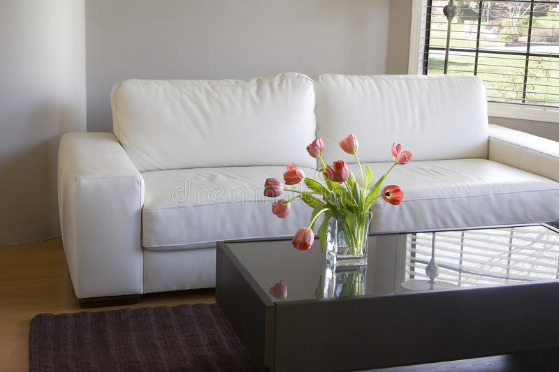 Red tulips in modern living room - home decor. Vase of red tulips in modern white living room - home decor royalty free stock photography