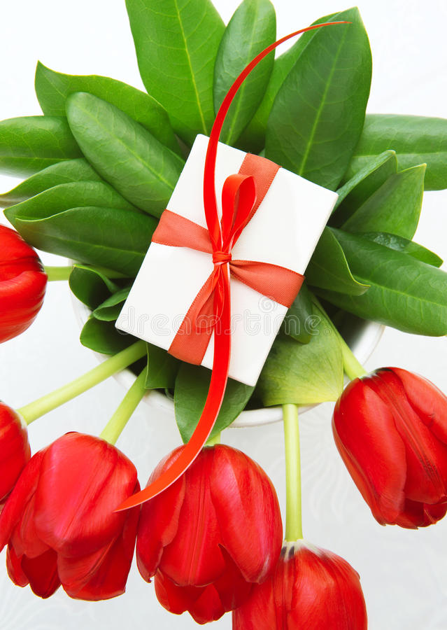 Red tulips for mom. Picture of red fresh tulip flowers with luxury present for mom, beautiful floral bouquet with little giftbox on the top on white background stock image