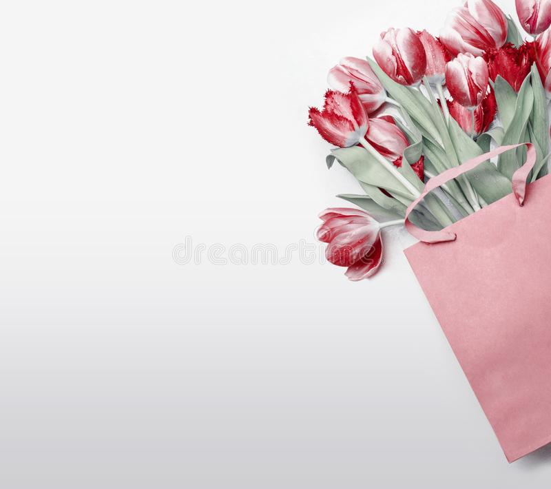Red tulips in paper shopping bag on light gray background. Festive spring flowers bunch. Floral gift composing. Springtime royalty free stock photo