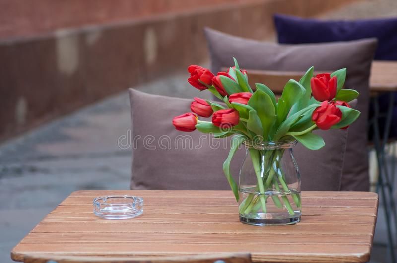 Red tulips on table in restaurant terrace in the street royalty free stock image