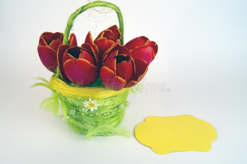 Red tulips in a yellow basket with a signature sheet royalty free stock image